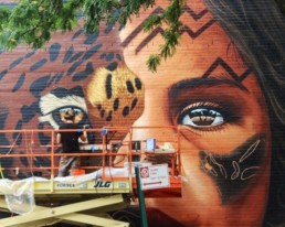 Sonny painting his Street Art Mural of Amazonian Girl and Jaguar Face Painted in Williamsburg, Brooklyn New York as part of Climate Week 2018 in partnership with UNICEF and Greenpoint Innovations